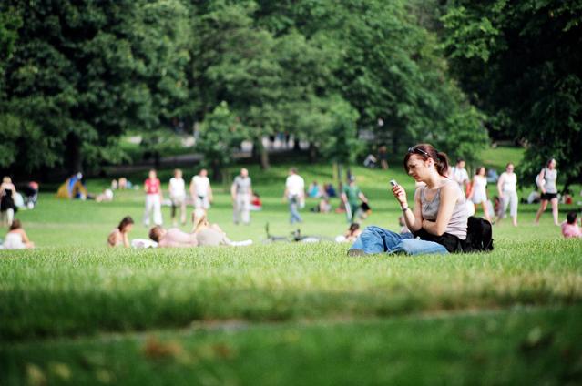 park, žena sedí na trávníku a má mobil v ruce